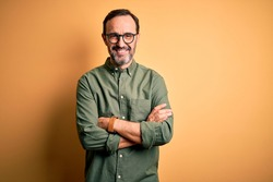 Middle age hoary man wearing casual green shirt and glasses over isolated yellow background happy face smiling with crossed arms looking at the camera. Positive person.