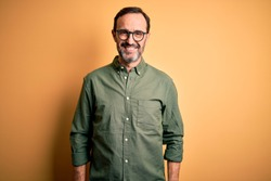 Middle age hoary man wearing casual green shirt and glasses over isolated yellow background with a happy and cool smile on face. Lucky person.