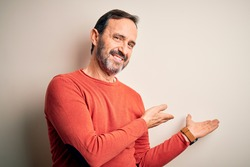 Middle age hoary man wearing casual orange sweater standing over isolated white background Inviting to enter smiling natural with open hand