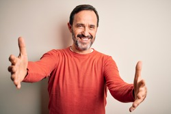 Middle age hoary man wearing casual orange sweater standing over isolated white background looking at the camera smiling with open arms for hug. Cheerful expression embracing happiness.