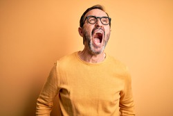 Middle age hoary man wearing casual sweater and glasses over isolated yellow background angry and mad screaming frustrated and furious, shouting with anger. Rage and aggressive concept.