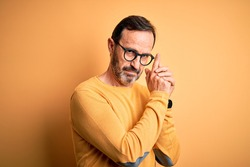 Middle age hoary man wearing casual sweater and glasses over isolated yellow background Holding symbolic gun with hand gesture, playing killing shooting weapons, angry face