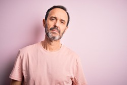 Middle age hoary man wearing casual t-shirt standing over isolated pink background Relaxed with serious expression on face. Simple and natural looking at the camera.