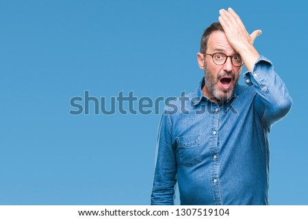 Middle age hoary senior man wearing glasses over isolated background surprised with hand on head for mistake, remember error. Forgot, bad memory concept.