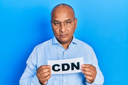 Middle age latin man holding cdn message paper relaxed with serious expression on face. simple and natural looking at the camera.