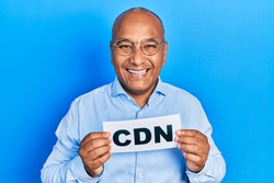 Middle age latin man holding cdn message paper smiling and laughing hard out loud because funny crazy joke.