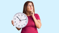 Middle age latin woman holding big clock serious face thinking about question with hand on chin, thoughtful about confusing idea