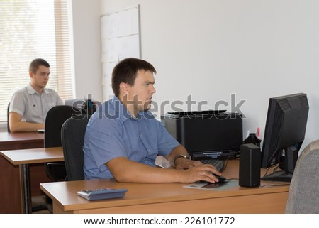 Middle Age Male Office Workers at their Designated Table Area Busy Working with Computer.