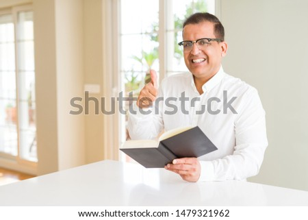 Middle age man reading a book at home wearing glasses happy with big smile doing ok sign, thumb up with fingers, excellent sign