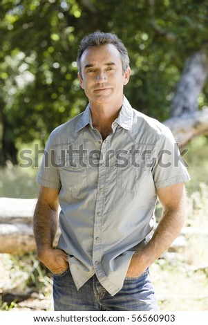Middle Age Man Standing Outdoors With Hand in Pockets
