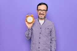Middle age man wearing glasses holding vintage alarm clock over isolated purple background looking positive and happy standing and smiling with a confident smile showing teeth