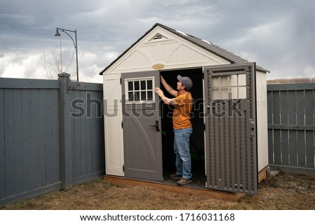 Middle age man wearing orange t shirt, jeans and baseball hat standing in doorway of his garden shed and fixing the door. A man finishes to build the backyard shed. Early spring garden work concept.