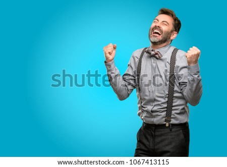 Middle age man, with beard and bow tie happy and excited expressing winning gesture. Successful and celebrating victory, triumphant