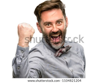Middle age man, with beard and bow tie happy and excited expressing winning gesture. Successful and celebrating victory, triumphant isolated over white background