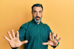 Middle age man with beard and grey hair wearing business clothes afraid and terrified with fear expression stop gesture with hands, shouting in shock. panic concept.
