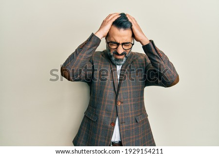 Middle age man with beard and grey hair wearing business jacket and glasses suffering from headache desperate and stressed because pain and migraine. hands on head.  Photo stock ©