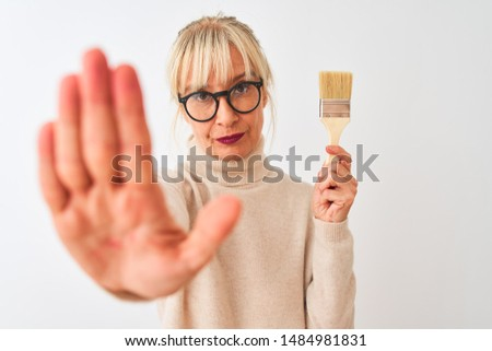 Middle age painter woman holding paint brush standing over isolated white background with open hand doing stop sign with serious and confident expression, defense gesture