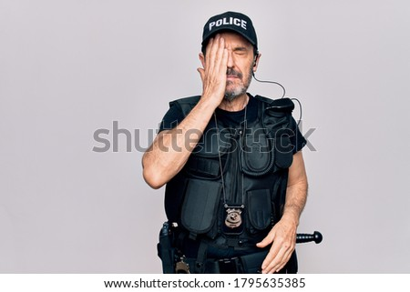 Middle age policeman wearing police uniform and bulletproof vest over white background surprised with hand on head for mistake, remember error. Forgot, bad memory concept. Stock photo ©