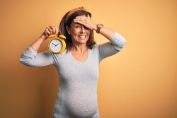 Middle age pregnant woman expecting baby at aged pregnancy holding alarm clock stressed with hand on head, shocked with shame and surprise face, angry and frustrated. Fear and upset for mistake.