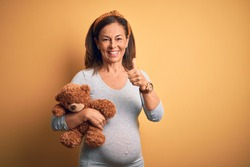 Middle age pregnant woman expecting baby holding teddy bear stuffed animal happy with big smile doing ok sign, thumb up with fingers, excellent sign
