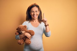 Middle age pregnant woman expecting baby holding teddy bear stuffed animal surprised with an idea or question pointing finger with happy face, number one
