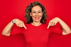 Middle age senior brunette woman wearing casual t-shirt standing over red background looking confident with smile on face, pointing oneself with fingers proud and happy.