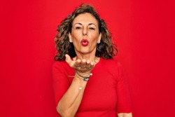 Middle age senior brunette woman wearing casual t-shirt standing over red background looking at the camera blowing a kiss with hand on air being lovely and sexy. Love expression.