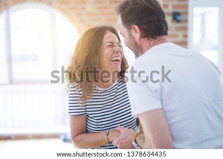 Middle age senior couple moving to a new house, smiling happy in love with apartmant