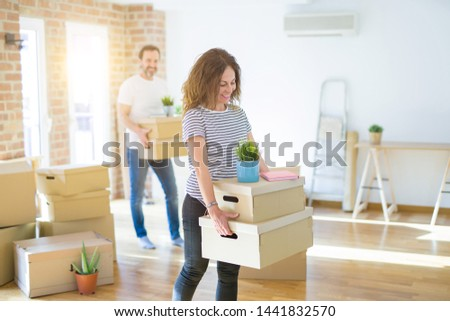 Middle age senior couple moving to a new house, smiling woman ho