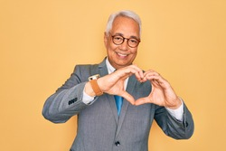 Middle age senior grey-haired handsome business man wearing glasses over yellow background smiling in love doing heart symbol shape with hands. Romantic concept.