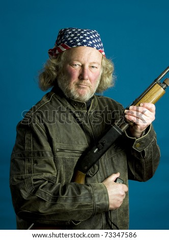 middle age senior long hair wearing leather jacket American flag bandanna  holding rifle firearm