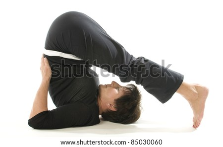 middle age senior woman demonstrating yoga position Halasana the plough