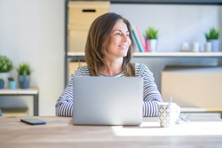 Middle age senior woman sitting at the table at home working using computer laptop looking away to side with smile on face, natural expression. Laughing confident.