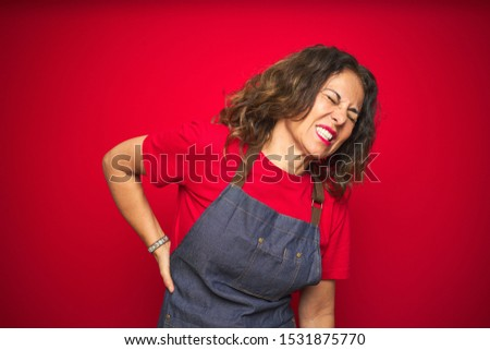 Middle age senior woman wearing apron uniform over red isolated background Suffering of backache, touching back with hand, muscular pain