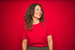 Middle age senior woman with curly hair over red isolated background looking away to side with smile on face, natural expression. Laughing confident.
