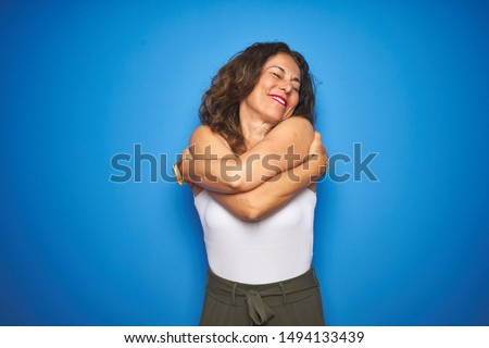 Middle age senior woman with curly hair standing over blue isolated background Hugging oneself happy and positive, smiling confident. Self love and self care Сток-фото ©