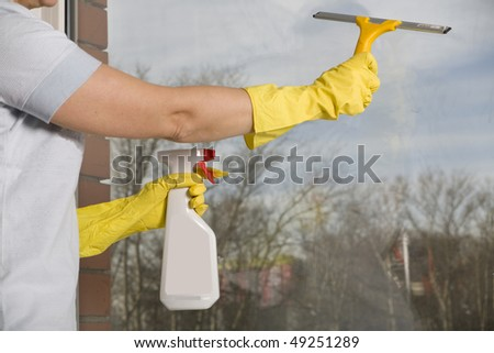 Middle Age Woman Cleaning the Window - stock photo