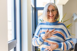 middle age woman laughing out loud at some hilarious joke, feeling happy and cheerful, having fun