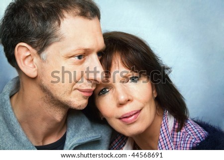 Middle-age woman lean on shoulder of her man , mature man is looking beside her