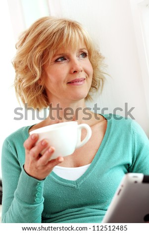 Middle age woman relaxing with tablet comper at home - stock photo