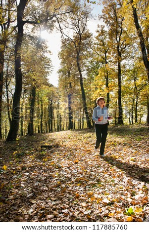 middle age woman running in the forest - stock photo