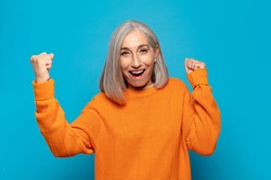 middle age woman shouting triumphantly, looking like excited, happy and surprised winner, celebrating