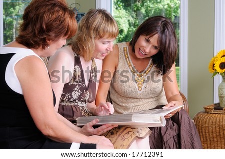 Middle Age Woman Showing Her Photo Album To Her Friends