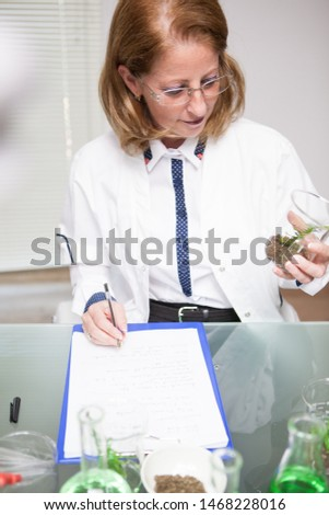 Middle age woman taking notes after testing microbiological tests on soil. Biologist working in a research lab.