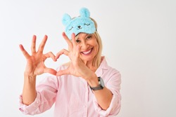 Middle age woman wearing blue sleep mask and pajama over isolated white background smiling in love showing heart symbol and shape with hands. Romantic concept.
