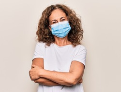 Middle age woman wearing coronavirus protection mask for covid-19 epidemic virus happy face smiling with crossed arms looking at the camera. Positive person.