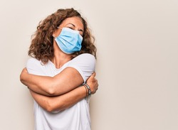 Middle age woman wearing coronavirus protection mask for covid-19 epidemic virus hugging oneself happy and positive, smiling confident. Self love and self care