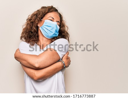 Middle age woman wearing coronavirus protection mask for covid-19 epidemic virus hugging oneself happy and positive, smiling confident. Self love and self care Сток-фото ©