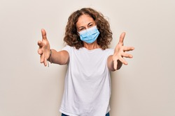 Middle age woman wearing coronavirus protection mask for covid-19 epidemic virus looking at the camera smiling with open arms for hug. Cheerful expression embracing happiness.