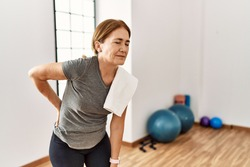 Middle age woman wearing sporty look training at the gym room suffering of backache, touching back with hand, muscular pain